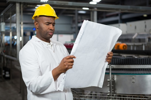 Male worker reading instructions at juice factory