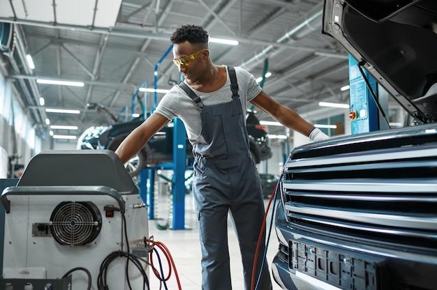 Работник-мужчина заправляет кондиционер, автосервис. ремонт автомобилей гараж, человек в форме, интерьер автомобильной станции