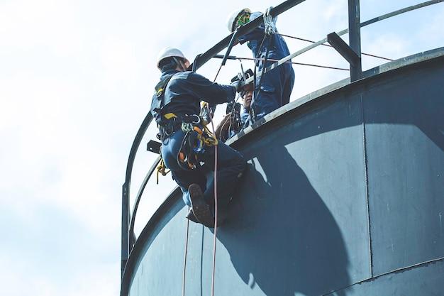 두께 저장 오일 및 가스 탱크 산업의 남성 작업자 로프 접근 높이 안전 검사