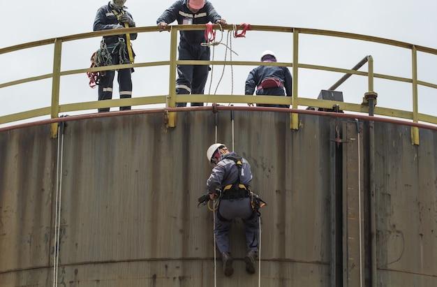 두께 저장 탱크 산업의 남성 작업자 로프 접근 검사.