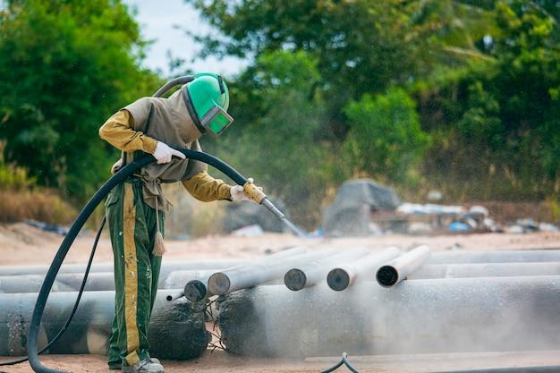 男性労働者工場で塗装する前に、鋼のパイプライン表面を洗浄するサンドブラストプロセス。