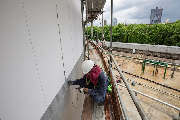 男性労働者の足場は、貯蔵タンクオイルの超音波厚さシェルプレートを検査するためのものです