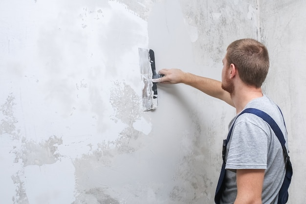 A male worker spreads the putty mixture and flattens the wall.
