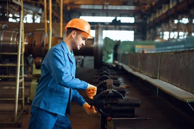 Рабочий-мужчина сжимает деталь в тисках на заводе, рабочее колесо турбины с лопатками