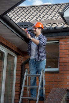 Male worker standing on step ladder in front of house