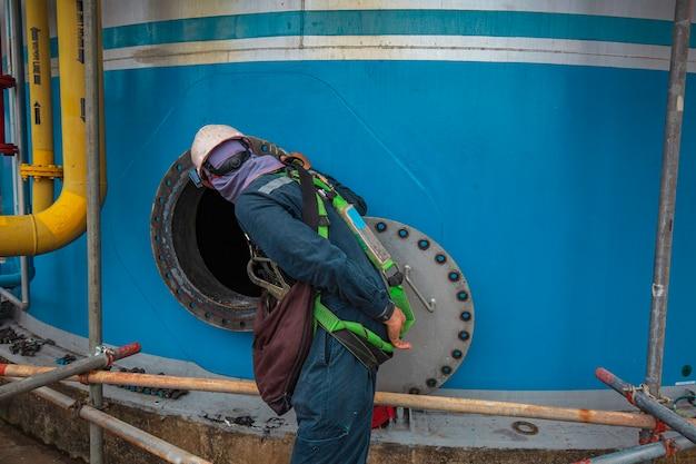 男性労働者は、燃料タンクのオイルエリアの限られたスペースの安全ブロワーの新鮮な空気のそばに立っています。