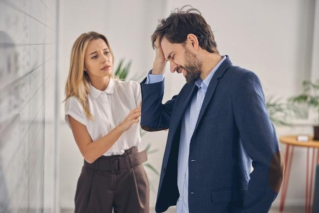 片頭痛に苦しんでいる男性労働者、心配そうな表情で彼を見ている女性の同僚