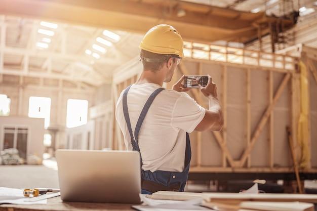 휴대 전화로 건물 사진을 찍는 남성 노동자