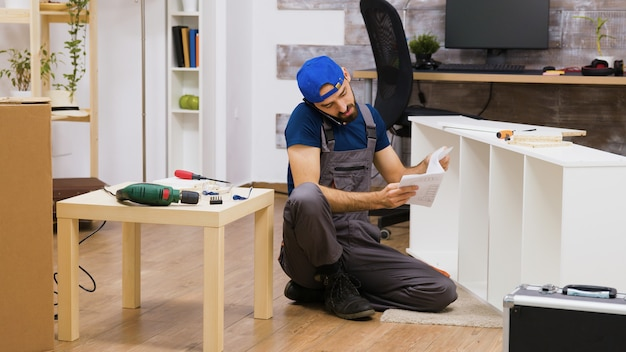 Male worker talking on the phone while assembles white furniture in new home. electric drill.