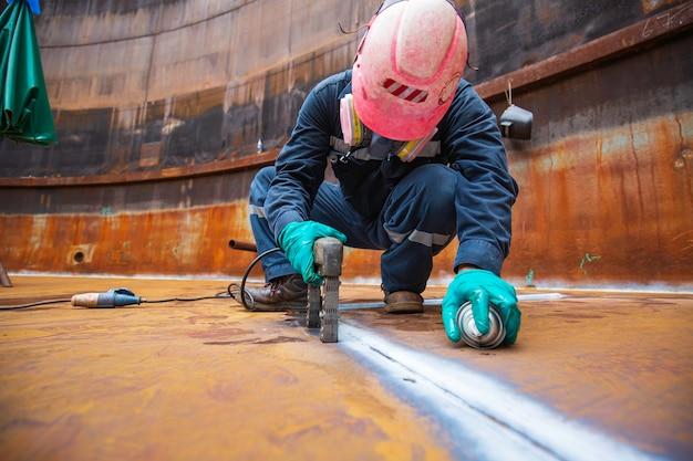 Мужчина рабочий тест стальной резервуар стыковой сваркой углеродистой нижней пластины резервуара для хранения нефти фон белый контраст теста магнитного поля