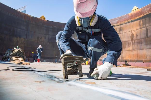 男性労働者試験鋼タンク突合せ溶接炭素底板貯蔵タンク油背景白磁場試験のコントラスト