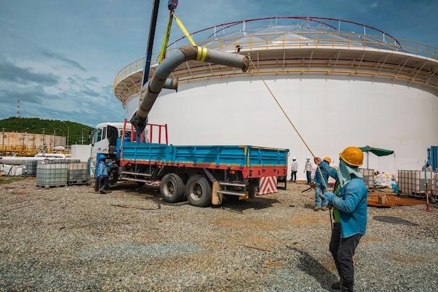남성 노동자 크레인 작업에서 슬링 어입니다. 생산 파이프라인 오일 및 밸브 장비의 크레인으로 하역.