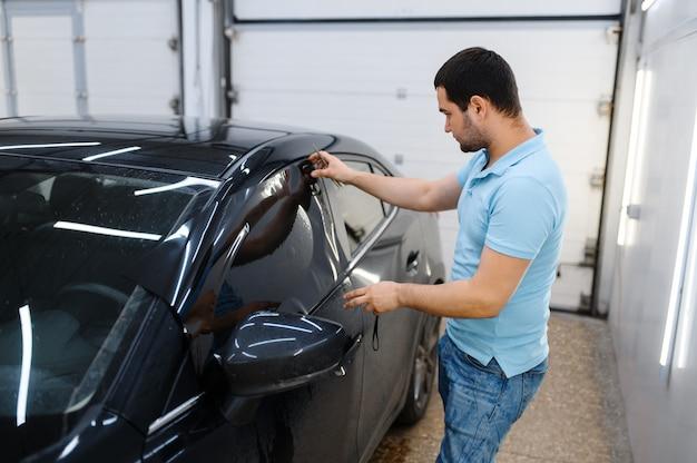 男性労働者は、濡れた車の色合い、チューニングサービスを試してみます。ガレージの車の窓にビニールの色合いを塗る整備士、色付きの自動車ガラス