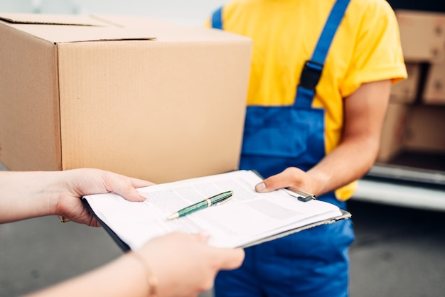 Male worker in uniform gives parcel to the client
