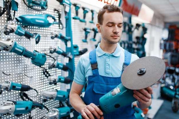 Male worker in uniform holds angle grinder in tool store. choice of professional equipment in hardware shop, instrument supermarket