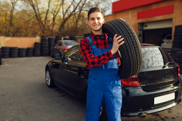 Male worker in uniform holds tyre, tire service
