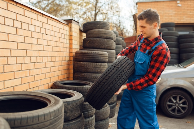 Male worker in uniform at the stack of tyres, tire service.