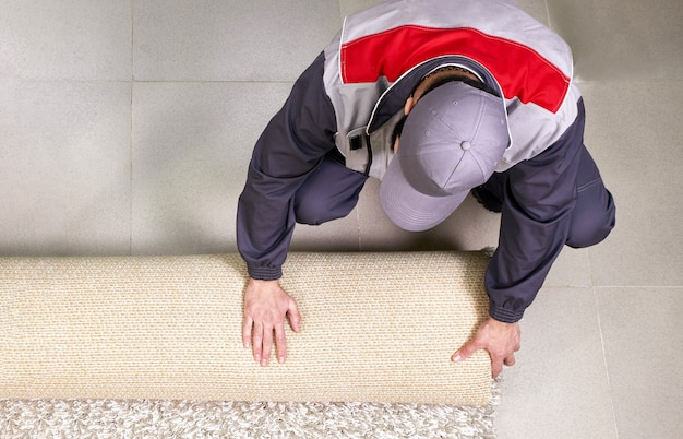 Male worker unrolling carpet on floor at home, view from above