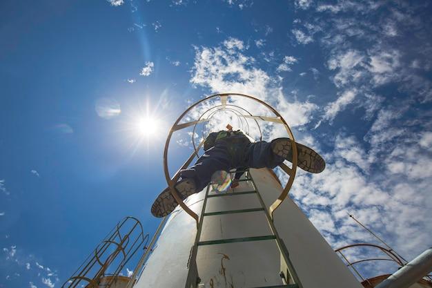はしごの上の男性労働者は、貯蔵タンク化学薬品の超音波厚さシェルプレート上部を検査するためのものです。