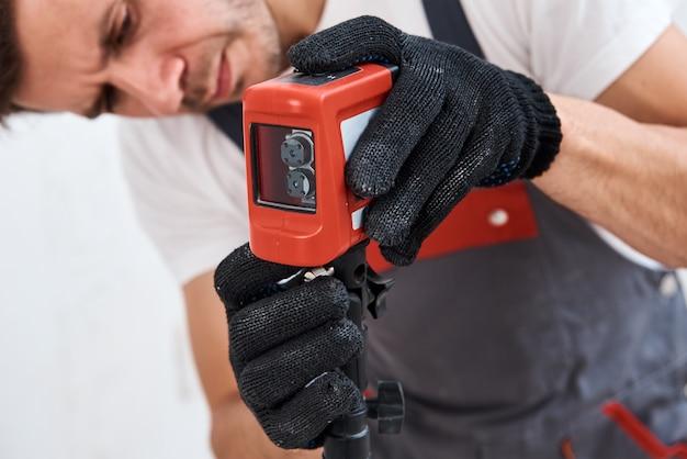 Мужчина-работник с помощью лазерного уровня