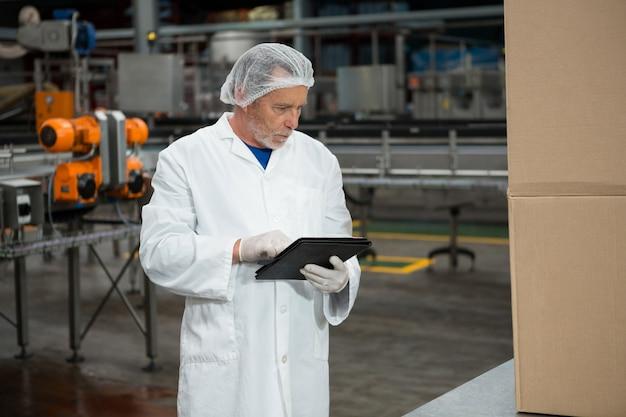 Мужчина-работник с помощью цифрового планшета на заводе холодных напитков