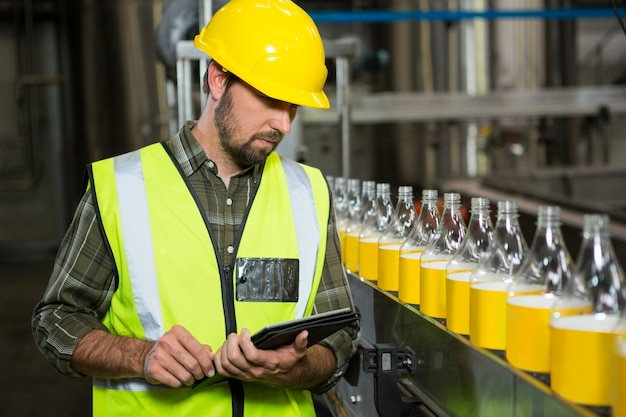 Male worker using digital tablet in juice factory