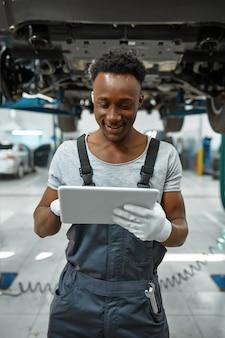 노트북을 사용하는 남성 작업자, 리프트에 자동차, 자동 서비스