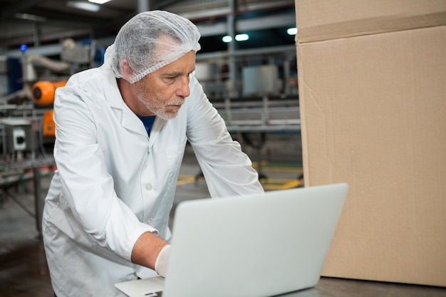 Male worker using laptop in cold drink factory