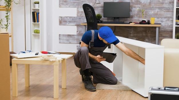 새 집에서 가구 조립을 위해 현대 기술을 사용하는 남성 노동자. 태블릿 컴퓨터와 작업자입니다.