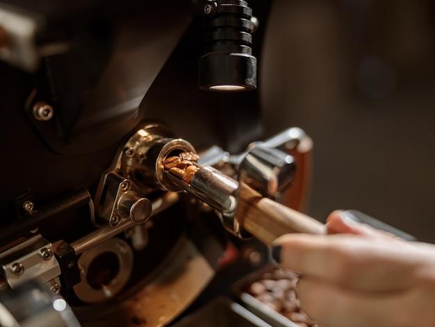 전문 커피 로스팅 기계를 사용하는 남성 작업자