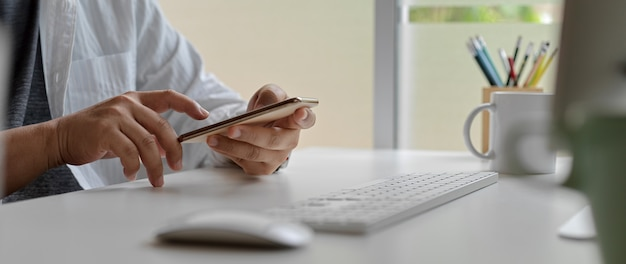 Male worker using smartphone while sitting at office desk with computer device and other supplies