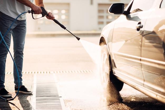 Работник-мужчина мыть машину с мойкой высокого давления