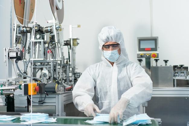 男性労働者は、衛生マスク製造工場で働く個人用保護具またはppeを着用します