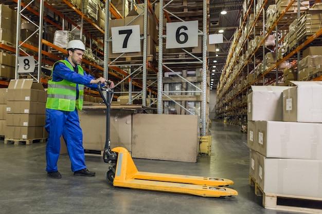 Рабочий-мужчина в синей униформе и каске ведет тележку с поддонами к поддонам с коробками.