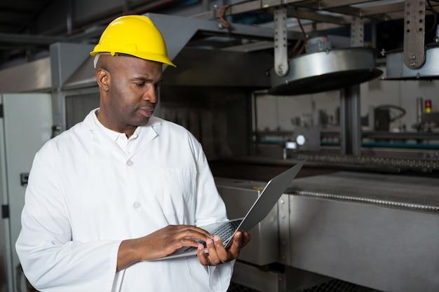 ジュース工場でラップトップを使用しながら白衣を着ている男性労働者