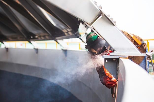 保護服と梁の屋根の修理を身に着けている男性労働者は、限られたスペース内で産業建設の石油とガスまたは貯蔵タンクを溶接します。