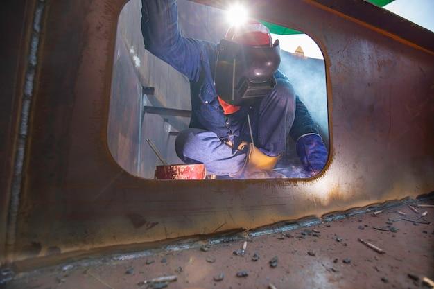 保護服を着てポンツーンマンホール溶接を修理する男性労働者は、限られたスペース内で産業建設用オイルフロート貯蔵タンクを煙で覆います。