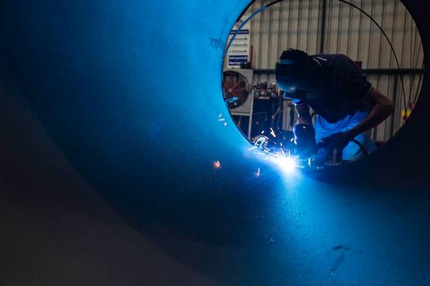 Мужчина-рабочий в защитной одежде и ремонтирует искры при сварке, промышленное строительство, нефть и газ, или трубопровод в замкнутых пространствах.