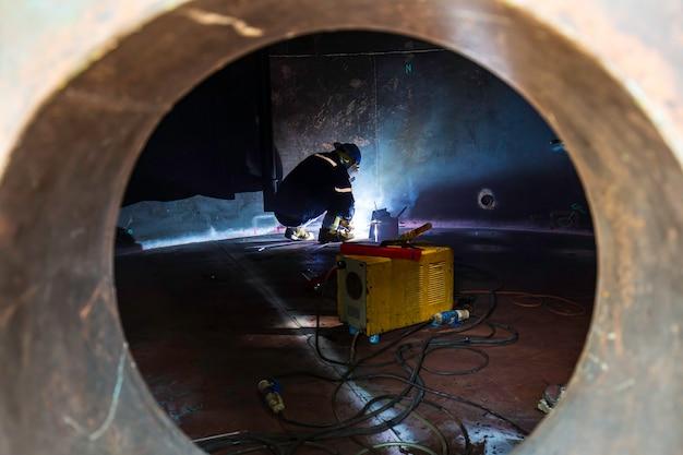 Мужчина-рабочий в защитной одежде и ремонт сварочных искр промышленное строительство резервуар тяжелой нефти в замкнутых пространствах.