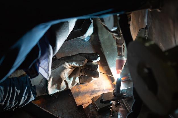 Мужской рабочий в защитной одежде ремонтной трубы из нержавеющей аргонной сварки промышленного строительства
