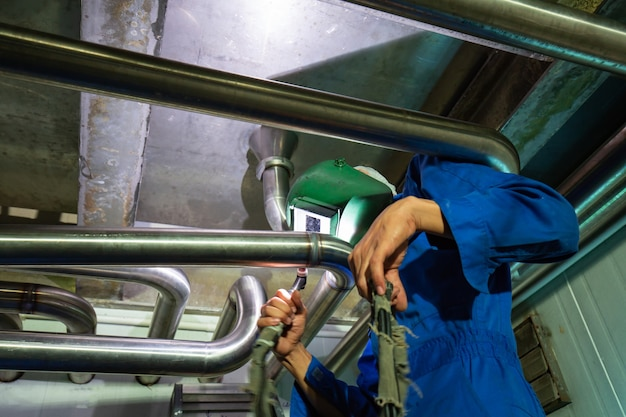 Male  worker wearing protective clothing of repair pipe stainless argon welding industrial construction modern milk cellar with stainless steel