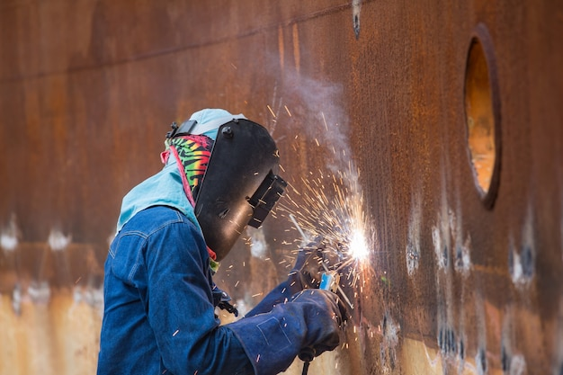 Male  worker wearing protective clothing and repair welding spark shell plate industrial construction oil and gas or  storage tank inside confined spaces.