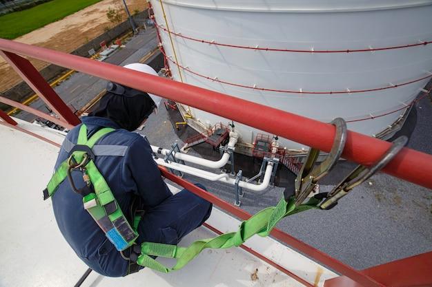 오픈 탑 탱크 루프 오일에 높은 난간 장소에서 작업 안전 첫 번째 하네스와 안전 외로운 남성 노동자