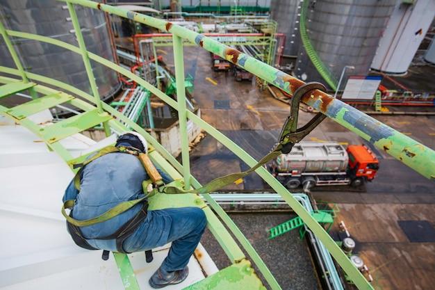 안전 제일의 하네스와 안전 외톨이를 착용한 남성 근로자는 상단 지붕 탱크 화학 물질의 높은 난간 위치에서 작업합니다.