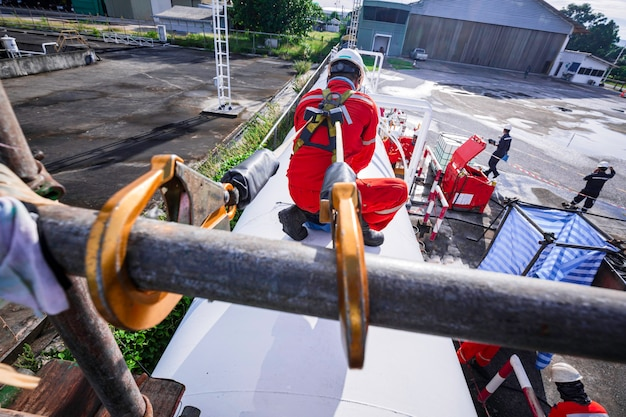 오픈 탑 탱크 루프 오일의 높은 비계 장소에서 일하는 안전 제일의 하네스와 안전 외로운 남성 노동자