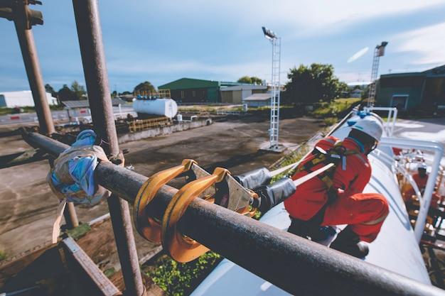 安全第一ハーネスと安全孤独を身に着けている男性労働者は、オープントップタンクルーフオイルの高い足場の場所で働いています