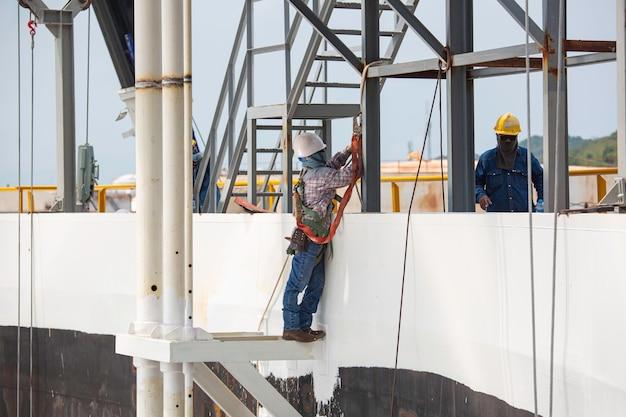 安全第一ハーネスと安全孤独を身に着けている男性労働者は、トップタンクルーフオイルの高い足場の場所で働いています