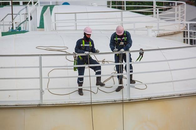 安全第一ハーネスとオープントップタンクルーフオイルの高い手すりの場所で働く安全を身に着けている男性労働者