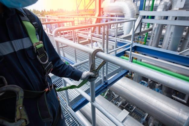 높은 곳에서 작업하는 안전 하네스 후크와 안전 라인 난간을 착용하는 남성 작업자 프리미엄 사진