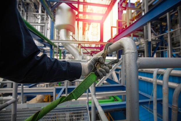 高所で働く安全ハーネスフックと安全ライン手すりを身に着けている男性労働者